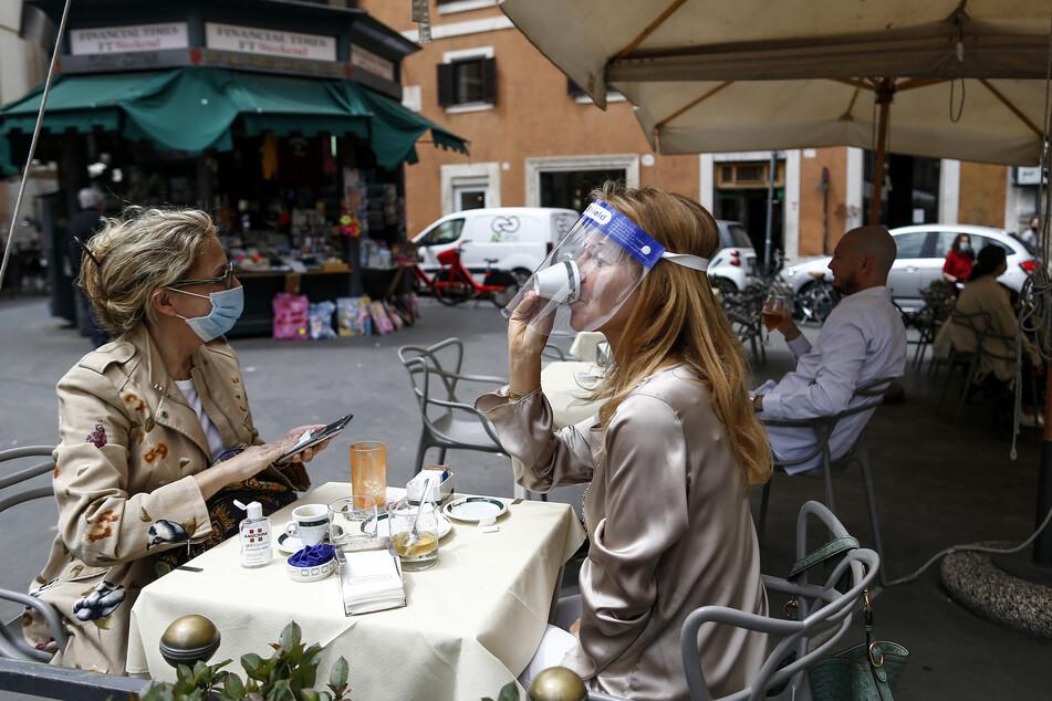 Rom: Die Besucherin eines Cafés schlürft ihren Kaffee unter ihrem Gesichtsschutz, während ihre Begleitung ihr Handy desinfiziert. Österreich und Italien sind von der Bundesregierung fast komplett als Risikogebiet eingestuft wurden.
