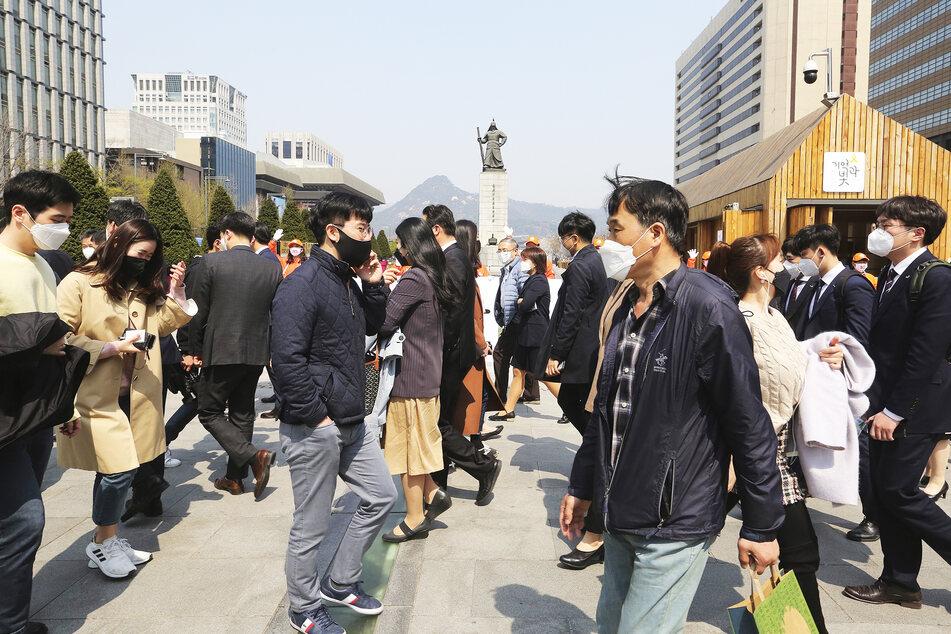 Menschen, die zum Schutz vor dem neuen Coronavirus eine Maske tragen, gehen über einen Fußgängerüberweg.