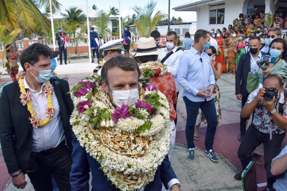 Emmanuel Macron trägt bei seiner Ankunft auf dem Manihi-Atoll, 500 km nordöstlich von Tahiti, Französisch-Polynesien im Pazifischen Ozean einen Blumenkranz und Muschelketten.