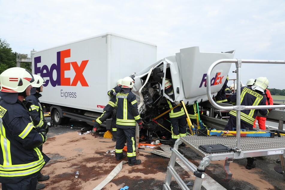 Die Einsatzkräfte untersuchen die stark demolierte Fahrerkabine.
