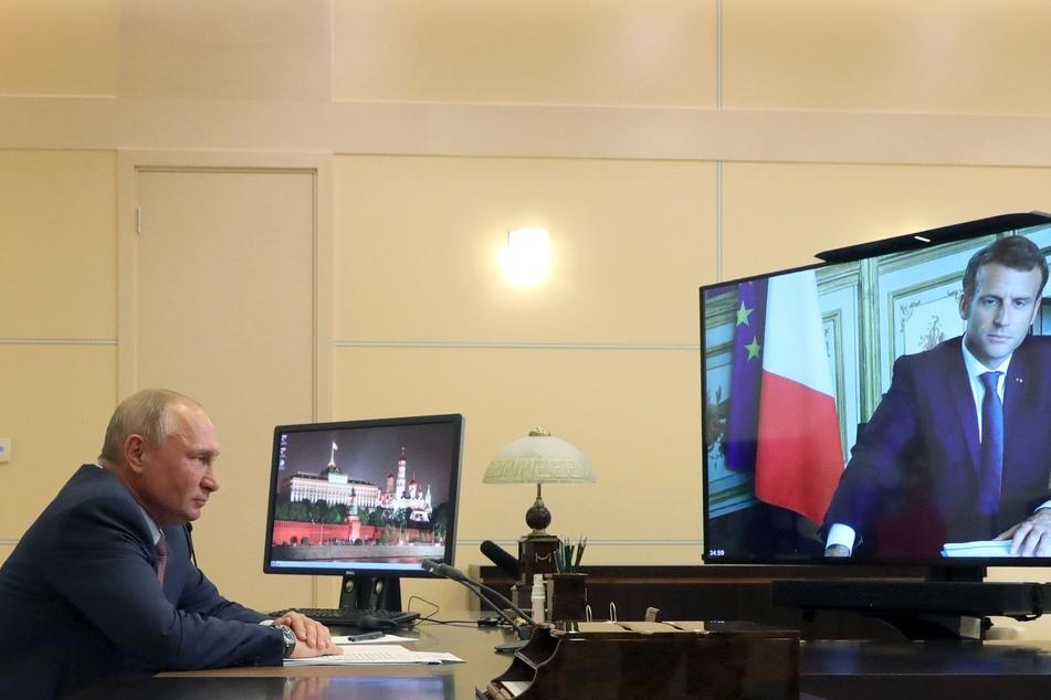 Wladimir Putin (l), Präsident von Russland, spricht per Videokonferenz mit Emmanuel Macron (r), Präsident von Frankreich, in der Residenz Nowo-Ogarjowo. Es geht vor allem um internationale Krisen wie die Corona-Pandemie, und Konflikte in Syrien, Libyen oder in der Ukraine.