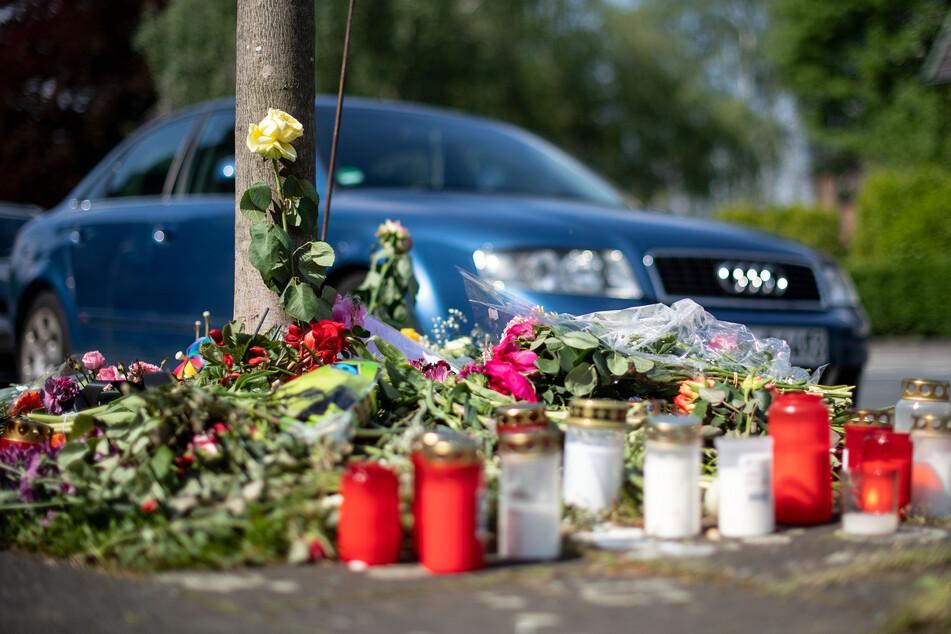 Blumen und Kerzen stehen an der Stelle in Moers, an der 2019 eine unbeteiligte Frau bei einem Autorennen zweier Männer getötet wurde.