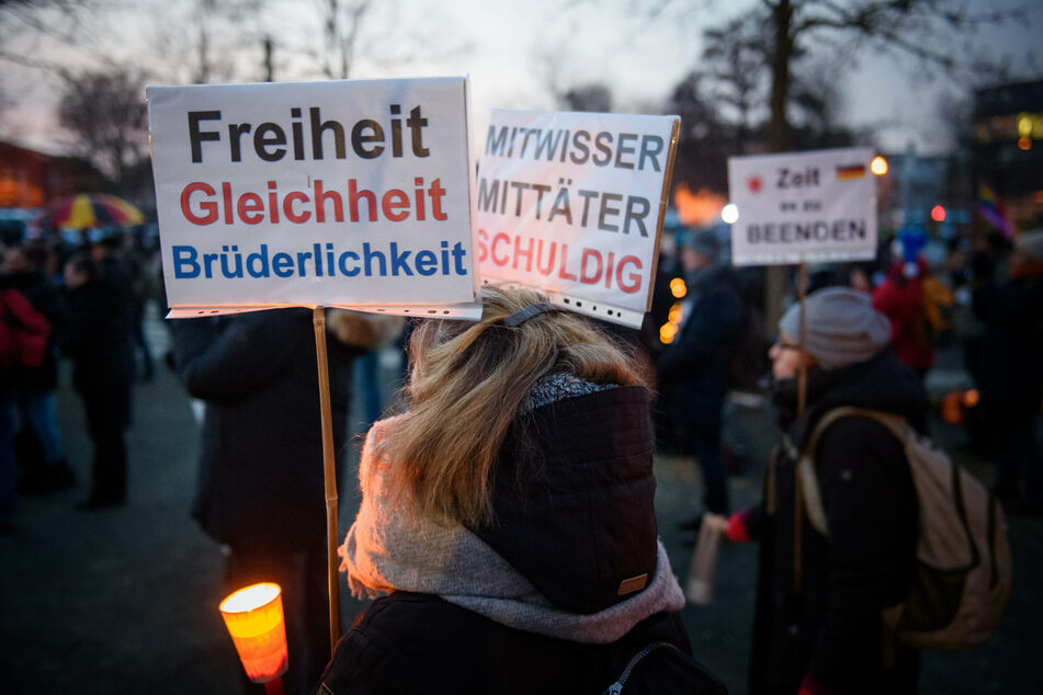 """Gegner der Corona-Maßnahmen stehen mit Schildern (""""Freiheit, Gleichheit, Brüderlichkeit"""") auf einer Protestkundgebung auf dem Berta-Klingberg-Platz in Schwerin."""