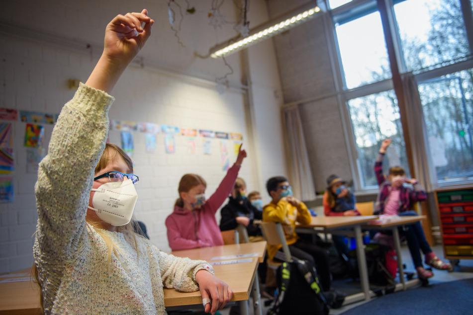 Eine Schülerin hebt an einer Grundschule in Kiel die Hand. Nach den Sommerferien soll an den Schulen die Normalität zurückkehren.