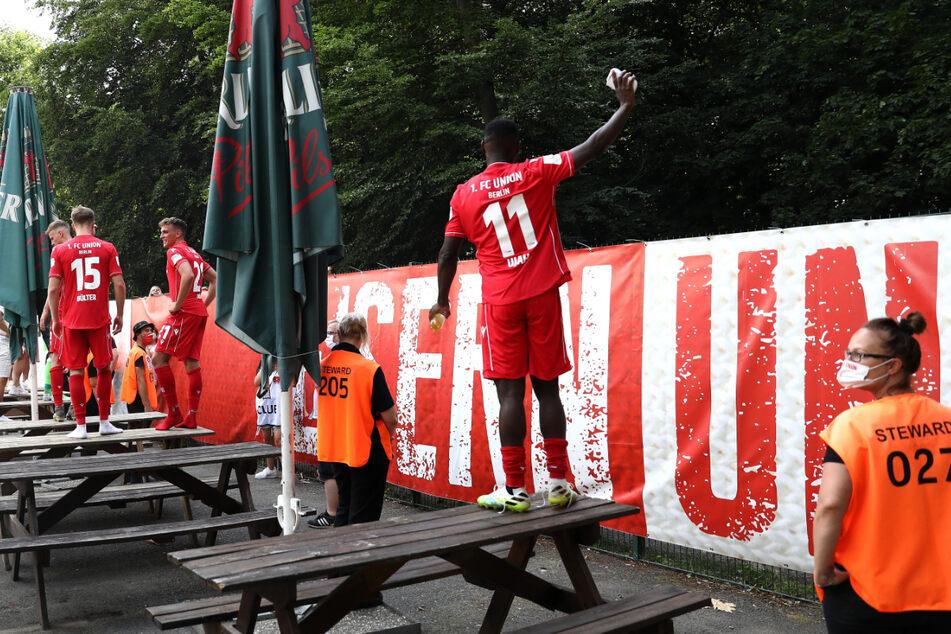 Anthony Ujah von Union Berlin feiert nach dem Spiel mit den Fans außerhalb des Platzes.