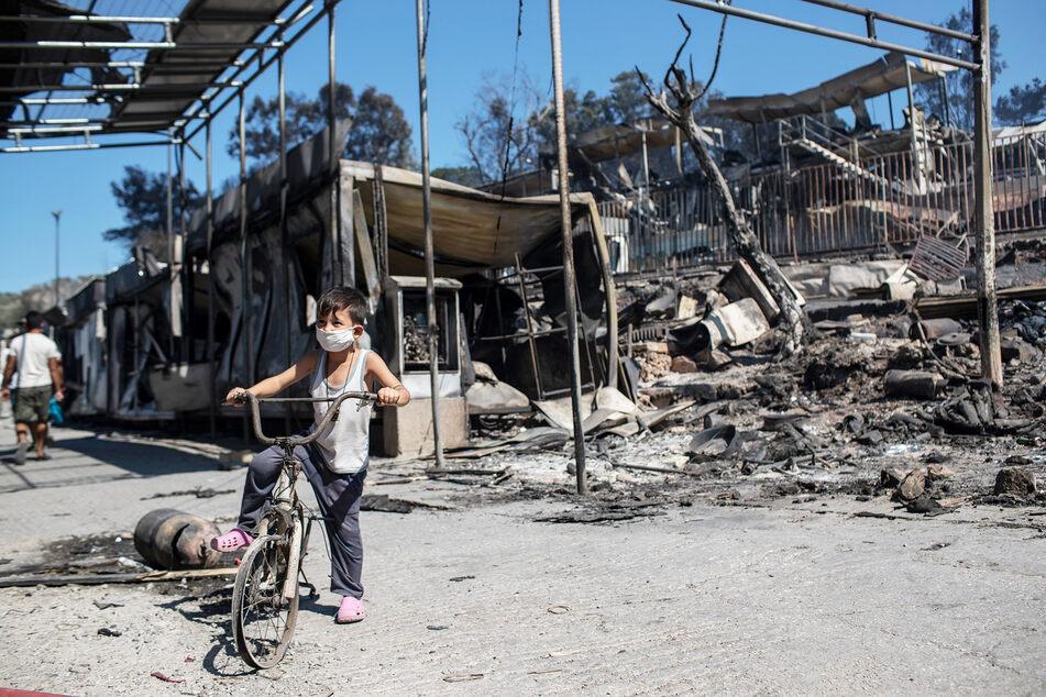 Ein Junge fährt mit einem beschädigten Fahrrad neben den verbrannten Trümmern des Flüchtlingslagers.
