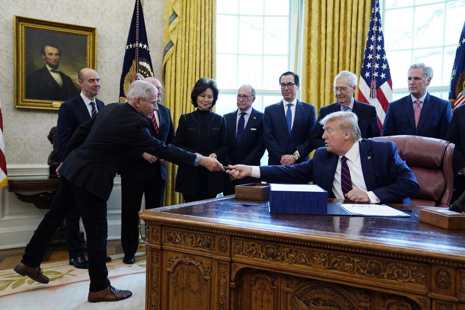 Am Freitag in Washington: Donald Trump (re.) überreicht Dr. Anthony Fauci (li.), dem Direktor des National Institute of Allergy and Infectious Diseases, einen Stift... Abstand: 2 Zentimeter.