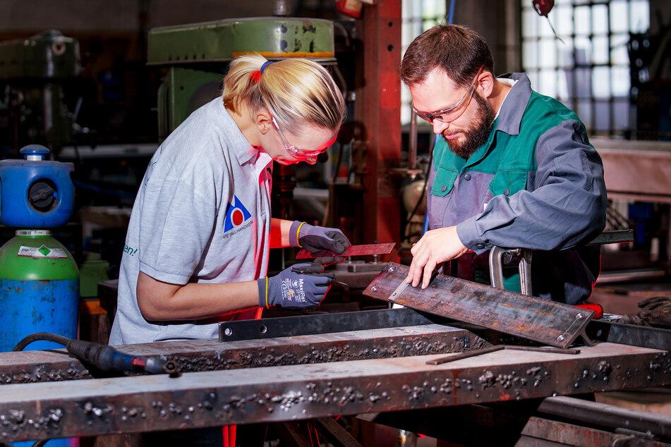 Geschäftsführer Markus Winkler und seine Frau prüfen ein Werkstück in ihrer Werkstatt.