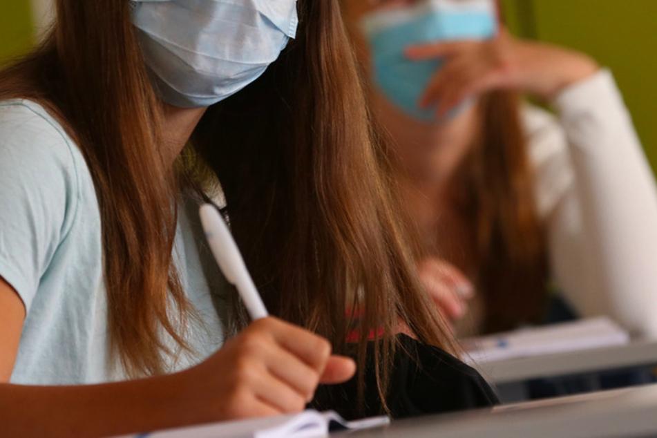 Schülerinnen einer neunten Klasse einer Mittelschule sitzen am ersten Schultag zu Beginn des Unterrichts mit Mundschutz im Klassenzimmer.