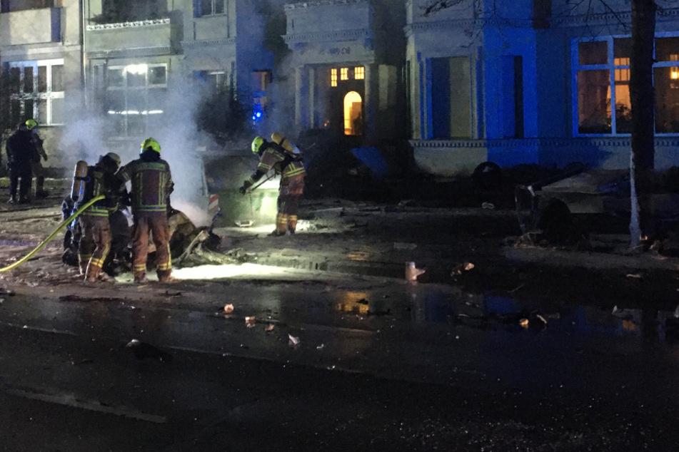 Feuerwehrkräfte löschen das brennende Auto.