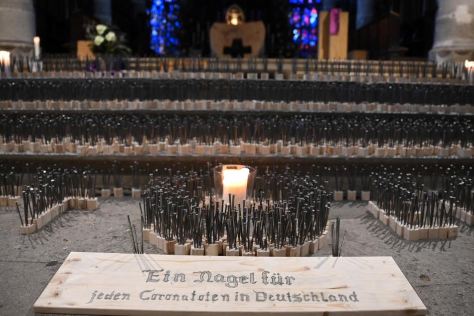 """Nägel stehen im Heilig-Kreuz-Münster in einem Kunstwerk aus 14434 Nägeln. Im Vordergrund liegt ein Schild, auf dem """"Ein Nagel für jeden Coronatoten in Deutschland"""" steht."""
