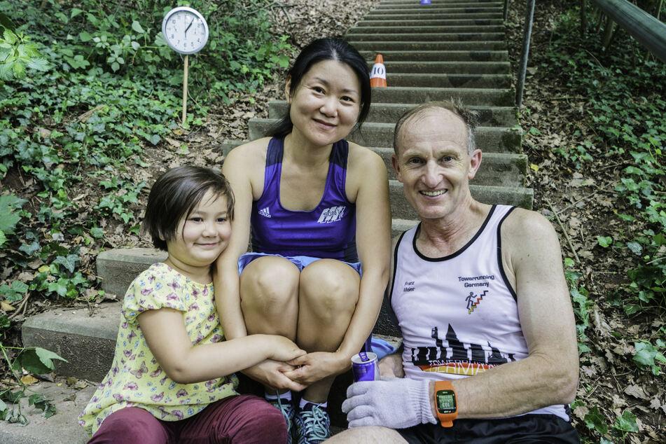 Tochter Letitia (l-r, 5), Xinxin Maier (39) und Franz Maier (58), beide aktuelle Weltrekordler im Treppensteigen, sitzen zusammen. Das Ehepaar aus Nußloch (Baden-Württemberg) hat einen erfolgreichen Weltrekordversuch im Treppensteigen für das Rekord-Institut für Deutschland (RID) abgelegt.