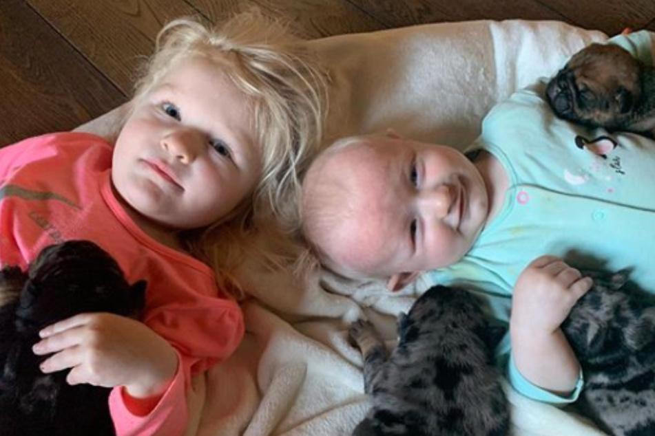 Das Bild zeigt Melanies (31) Kinder mit dem süßen Hundenachwuchs.