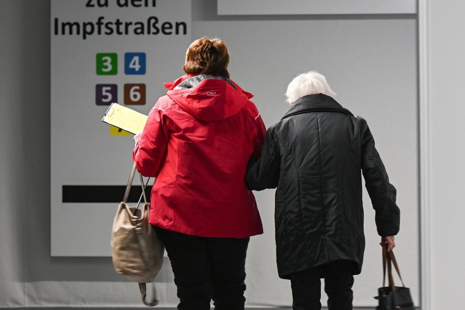 Hessen, Heuchelheim: Eine ältere Frau wird im Impfzentrum zu einer Impfkabine begleitet.
