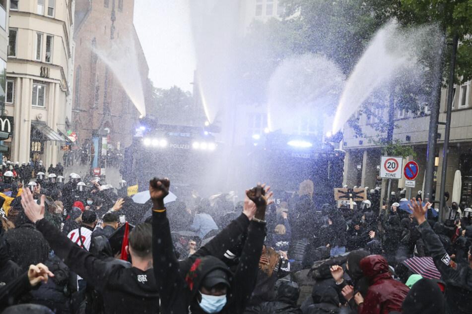 Unter Einsatz von zwei Wasserwerfern drängen Einsatzkräfte der Polizei Teilnehmer einer aufgelösten Demonstration zurück.
