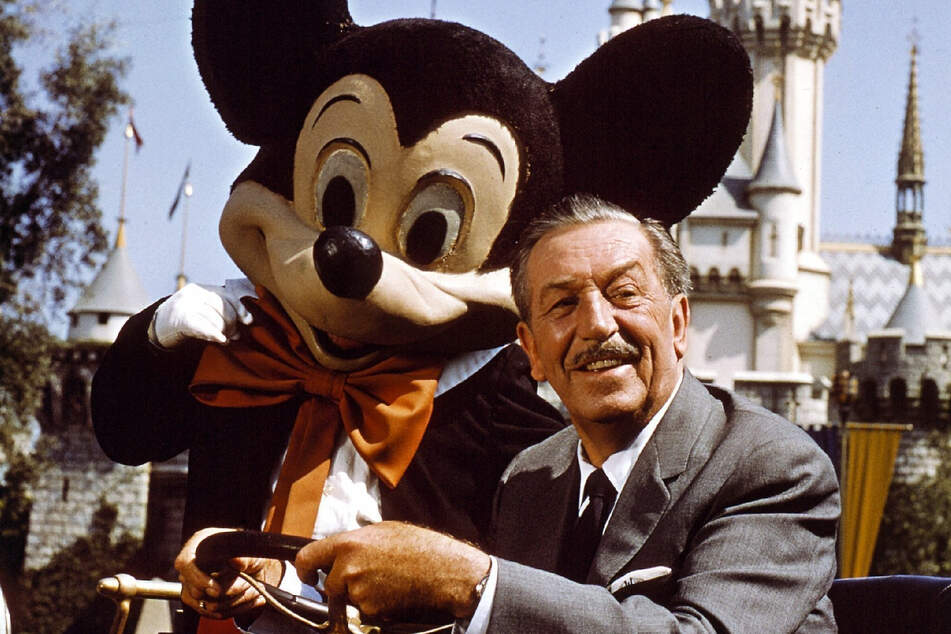 Walt Disney posiert mit einer Mickey-Mouse-Figur im Arm.