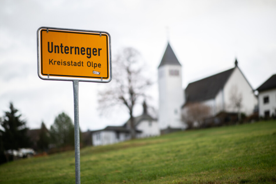 Das Ortsschild des Ortsteils Unterneger steht vor der St. Barbara- und St. Luzia-Kirche.