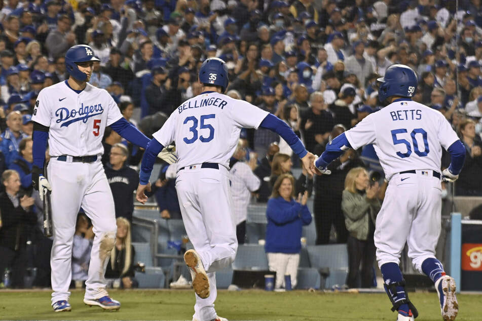 Cody Bellinger (c), Mookie Betts (r) and Corey Seager (l) celebrate as the Dodgers force game five of the NLDS on Thursday night.