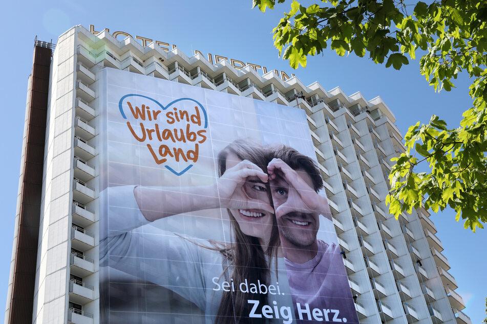 """Am Hotel Neptun hängt der erste Teil eines großen Transparents mit der Aufschrift """"Wir sind Urlaubsland""""."""