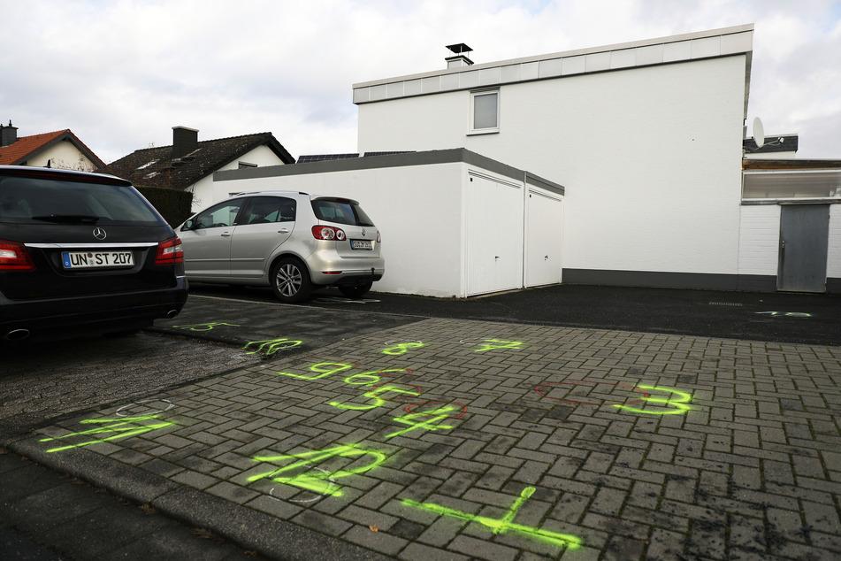 Markierungen der Spurensicherung der Polizei sind auf den Boden einer Hauseinfahrt gesprüht.