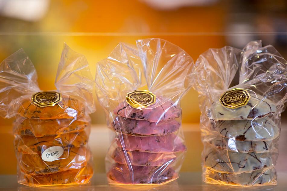 Drei Packungen Lebkuchen mit einem Überzug von Orangenschokolade (l), Erdbeerschokolade (M) und weißer Schokolade stehen in der Lebküchnerei Düll, auf der Theke.
