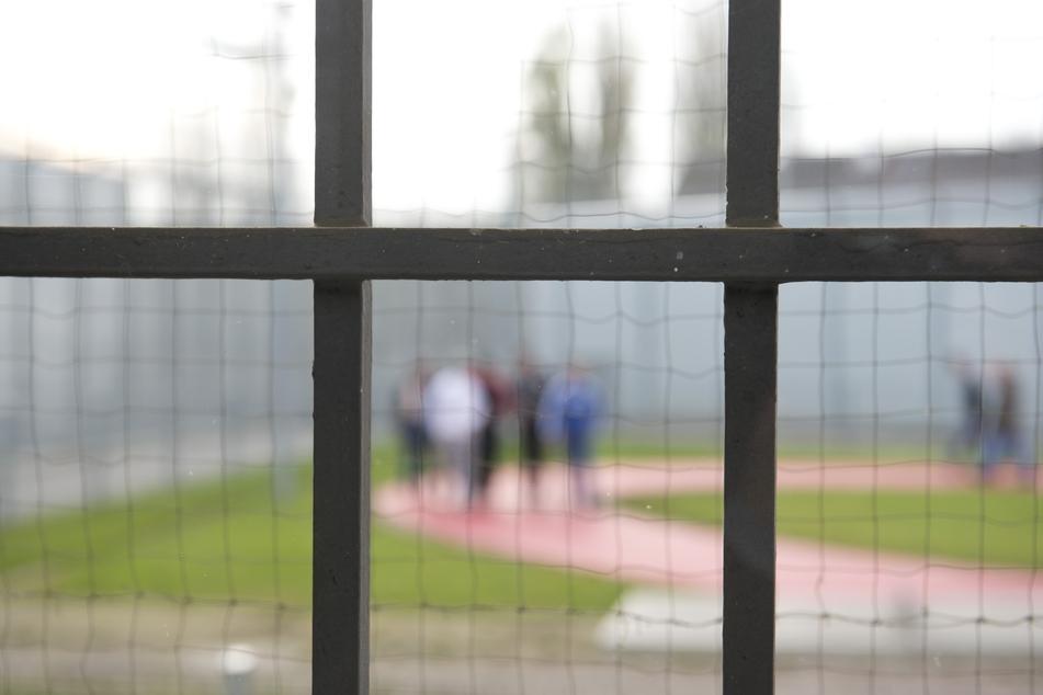 Hinter einem Gitter laufen Gefängnisinsassen einer Justizvollzugsanstalt über einen Gefängnishof. (Symbolbild)