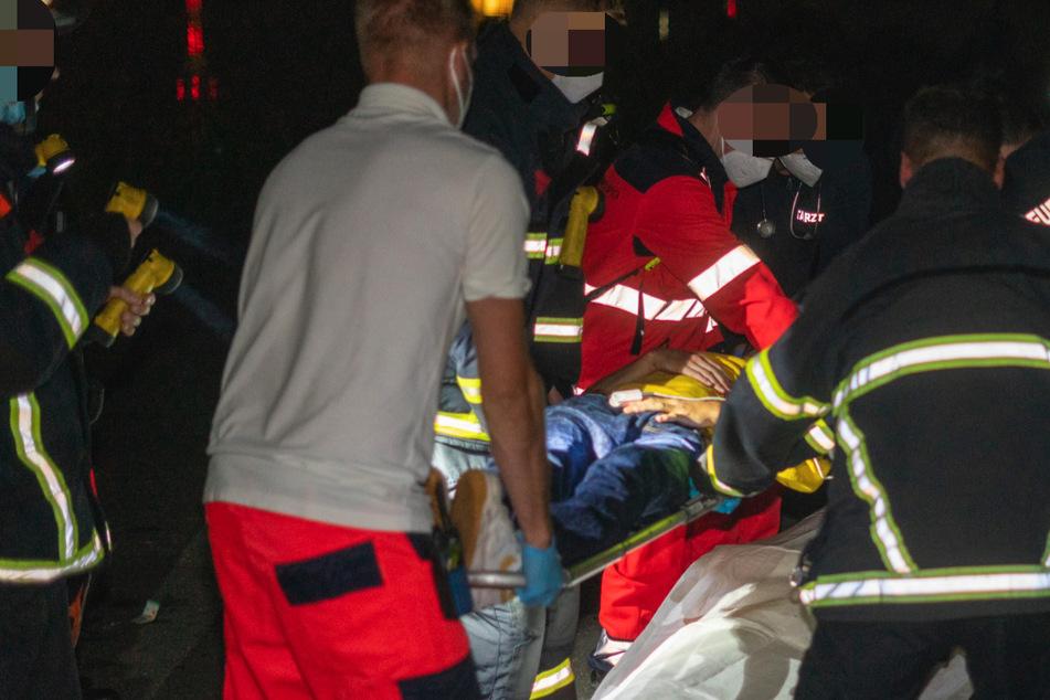 Rettungskräfte verlegen den Verletzten in einen Krankenwagen.