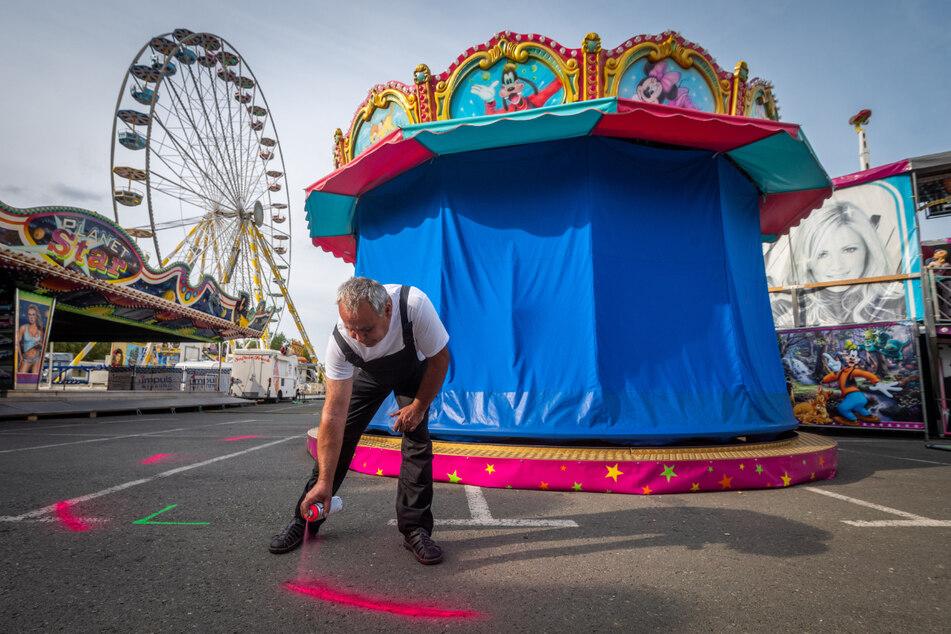 Feiern mit Abstand: Vor Beginn des Zwickauer Herbstvolksfestes im September 2020 auf dem Platz der Völkerfreundschaft markiert ein Mitarbeiter Abstandsmaße auf dem Boden.