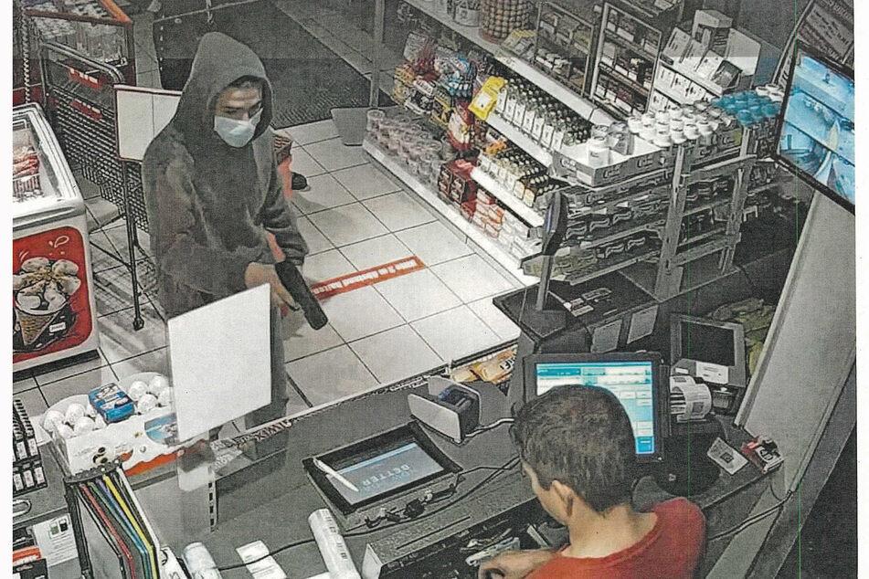 Einer der Räuber hat den Kassierer mit einer Pistole bedroht.