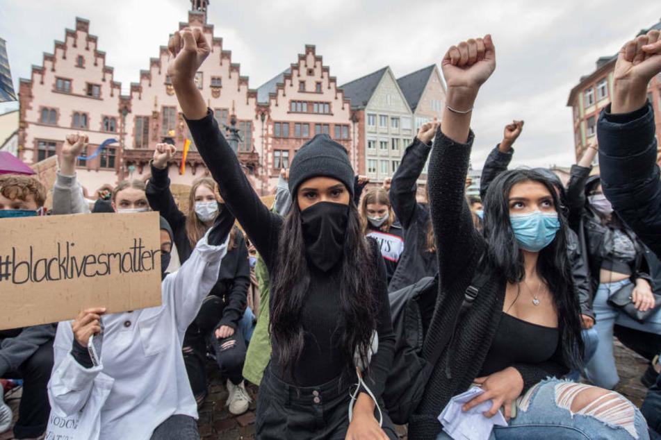 Auf Knien und mit in die Höhe gestreckter Faust bekunden Demonstranten auf dem Römerberg in Frankfurt ihre Solidarität mit den Anti-Rassismus-Protesten in den USA.