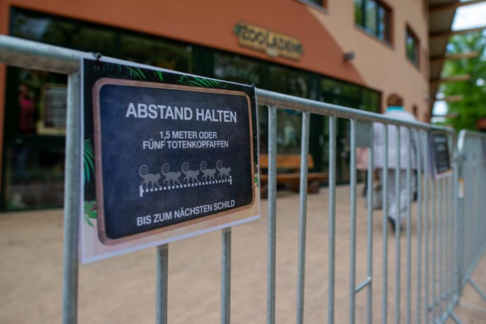 """Magdeburg: """"Abstand halten. 1,5 Meter oder fünf Totenkopfaffen"""" steht am Zooeingang auf einem Schild, das an einerm Gitter hängt. Das Gitter war aufgestellt worden, um die Besucherströme besser lenken zu können. Wegen der Ausbreitung des Corona-Virus musste der Zoo am 17. März 2020 jedoch schließen."""
