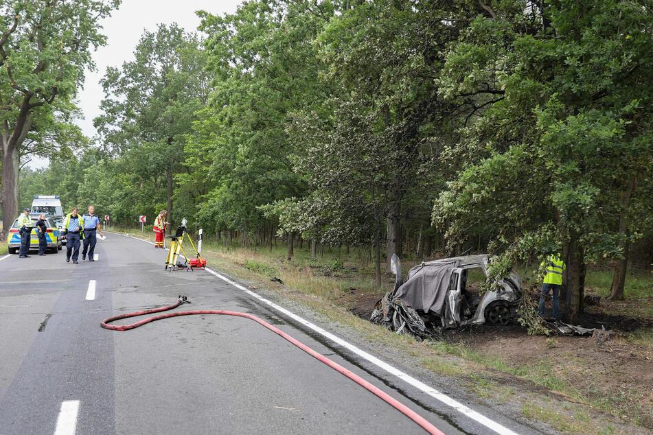 Die Einsatzkräfte vor Ort untersuchen das völlig zerstörte Fahrzeug.