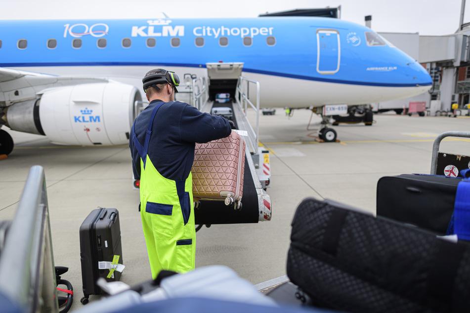 Dresden: Ein Mitarbeiter des Bodenpersonals räumt vor dem Start einer Maschine vom Typ Embraer der niederländischen Airline KLM vom Flughafen Dresden International nach Amsterdam-Schiphol Koffer auf ein Gepäckband.