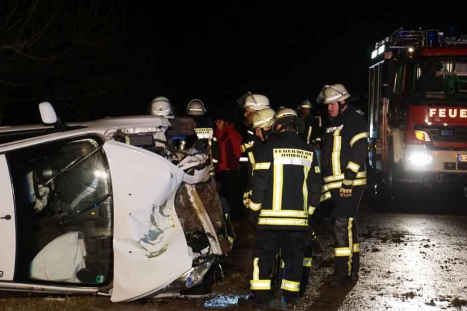 Feuerwehrmänner begutachten das am Unfall beteiligte Auto.