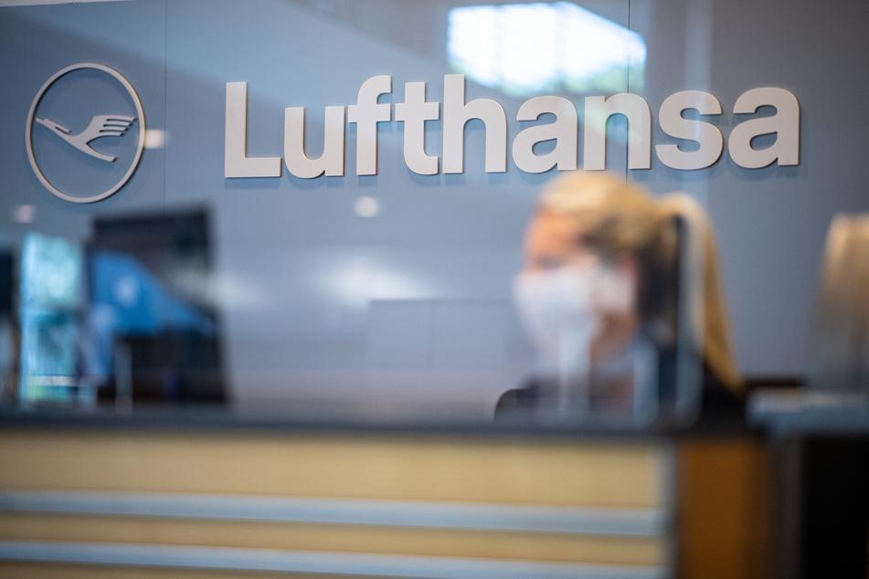 Eine Mitarbeiterin der Lufthansa sitzt mit ihrer Mund- und Nasenschutzmaske am Check-in im Flughafen Münster-Osnabrück. Die Lufthansa will ihr fliegendes Personal vollständig gegen Corona impfen lassen.