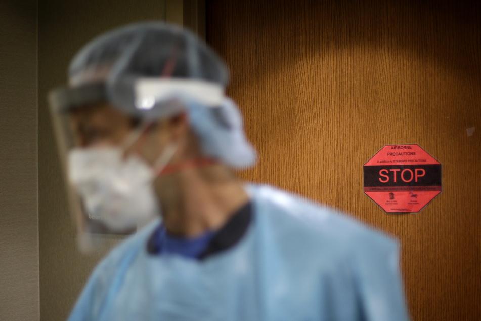 Ein Arzt spricht vor dem Zimmer eines Covid-19-Patienten mit dem Krankenhauspersonal. Weltweit haben die USA die höchste Zahl an Corona-Infektionen.