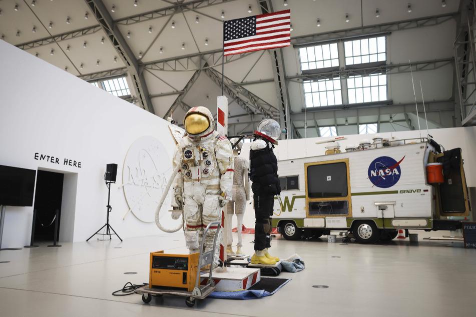 Weltraumanzüge und ein zur Quarantäne-Station umgebautes Wohnmobil sind in der Ausstellung zu sehen.