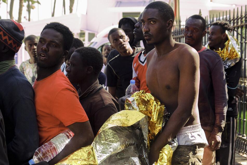 Afrikanische Migranten werden nach ihrer Ankunft an der Küste von der spanischen Polizei zu einer vorübergehenden Unterkunft gebracht.