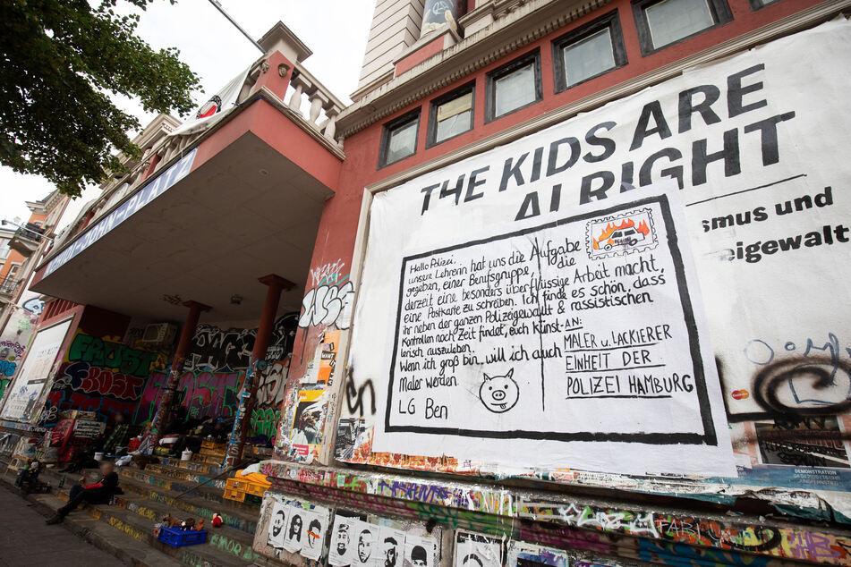 Ein Plakat mit einem kritischen Text klebt an einer Aussenwand des linksautonomen Kulturzentrums Rote Flora im Hamburger Schanzenviertel.