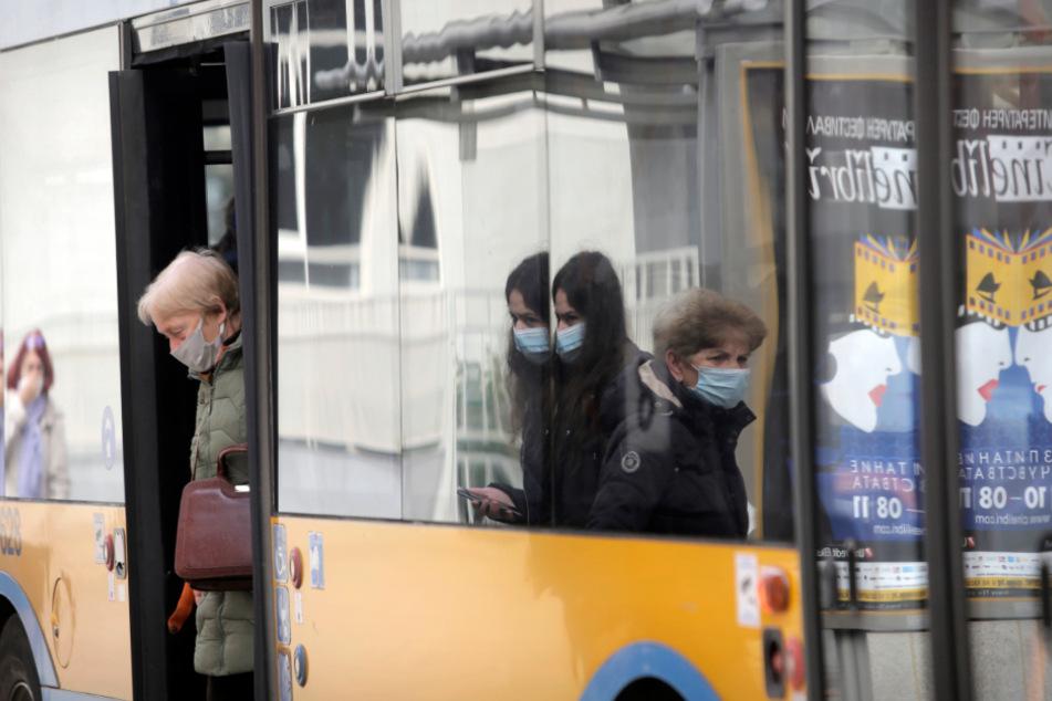 Fahrgäste tragen in Bulgarien Mund-Nasen-Bedeckungen und verlassen einen Bus, während andere darauf warten einzusteigen.