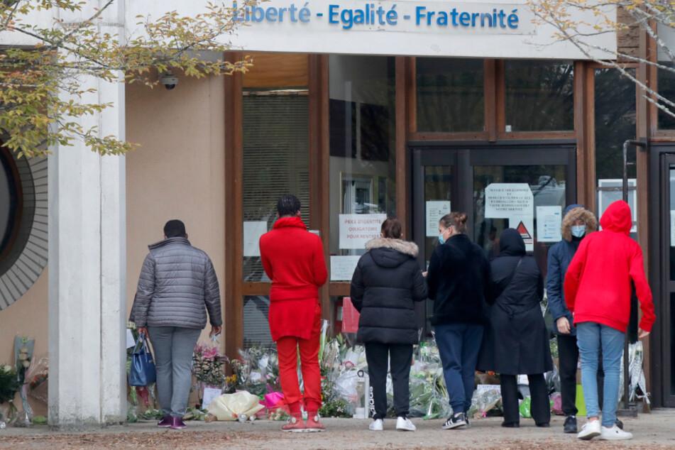 """Schüler gedenken vor einer Schule, auf der der Schriftzug """"Liberté - Egalité - Fraternité"""" (Freiheit - Gleichheit - Brüderlichkeit) zu lesen ist, einem Lehrer, der bei einer mutmaßlich terroristisch motivierten Tat ermordet wurde."""