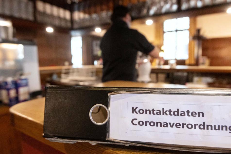 """Ein Ordner mit der Aufschrift """"Kontaktdaten Coronaverordnung"""" liegt in einer Gaststätte auf der Theke. (Symbolbild)"""