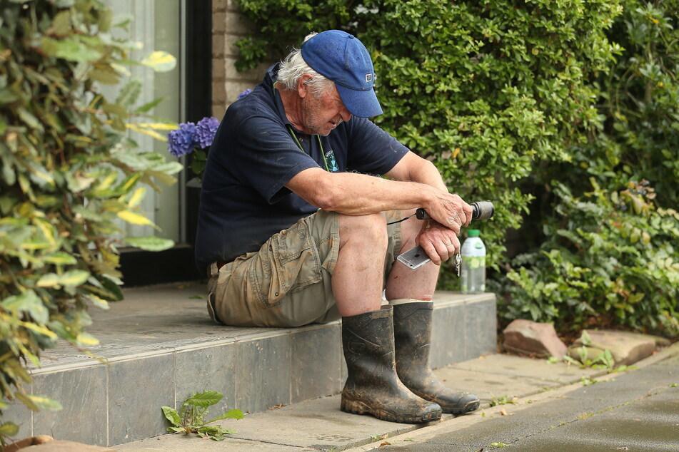 Mit gesenktem Kopf sitzt ein Mann vor seinem Haus im vom Hochwasser stark betroffenem Erftstadt-Blessem.