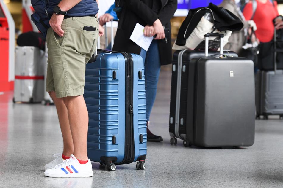 Flugreisende stehen in Terminal 1 des Frankfurter Flughafens am Check-in-Schalter an. (Symbolbild)