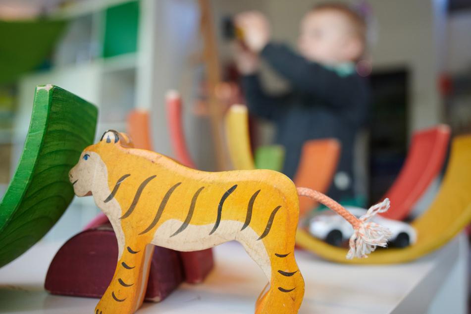 Ein Junge spielt in einem Kindergarten mit Bauklötzen und einem Spielzeugauto.