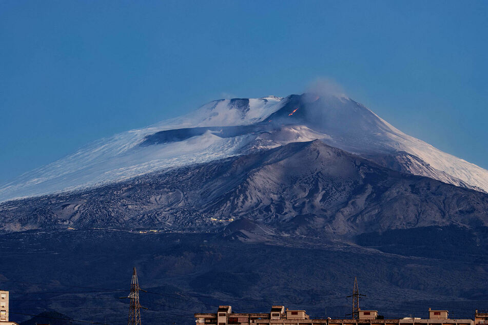 Smoke, lava, and ashes rise from Etna volcano in Sicily, Italy.