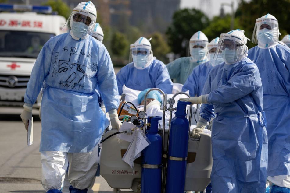 Wuhan: Medizinisches Personal in Schutzanzügen schieben einen Covid-19-Patienten in einem Bett über eine Straße. (Archivbild)