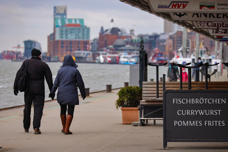 Bei trübem Wetter gehen Menschen an den Landungsbrücken spazieren. Auch in den kommenden Tagen bleibt es in der Hansestadt ungemütlich..