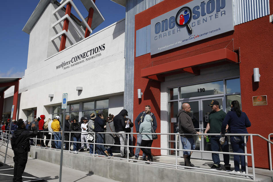 Menschen stehen in einer Schlange vor einem Job-Center um Arbeitslosenunterstützung zu beantragen.