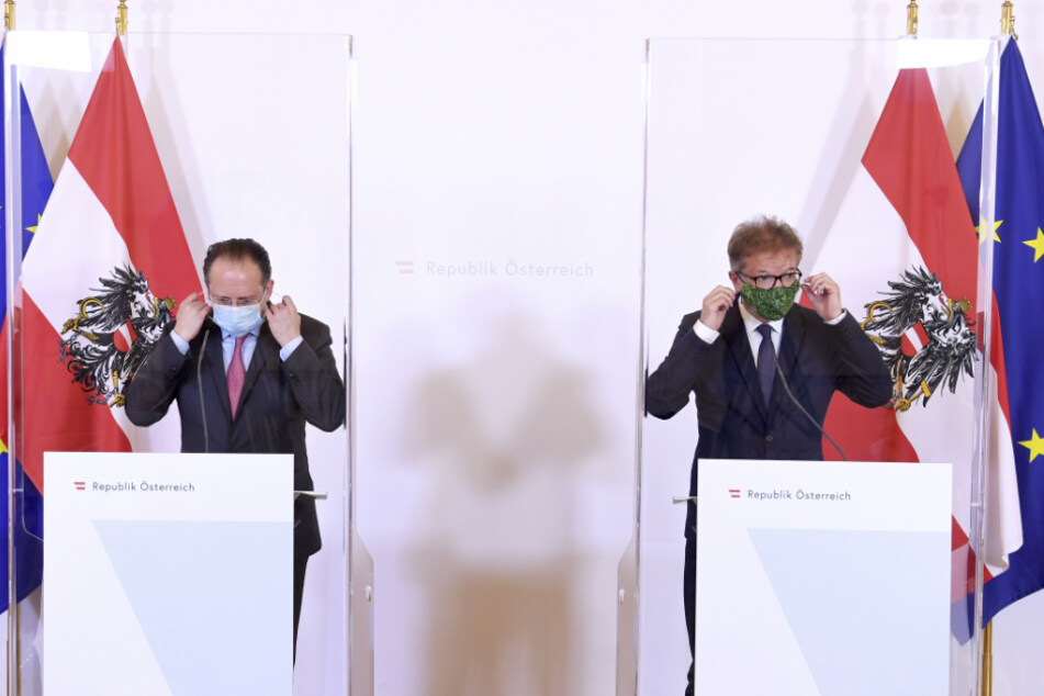 Alexander Schallenberg (l), Außenminister von Österreich, und Rudolf Anschober, Gesundheitsminister von Österreich, nehmen bei einer Pressekonferenz ihren Mundschutz ab.